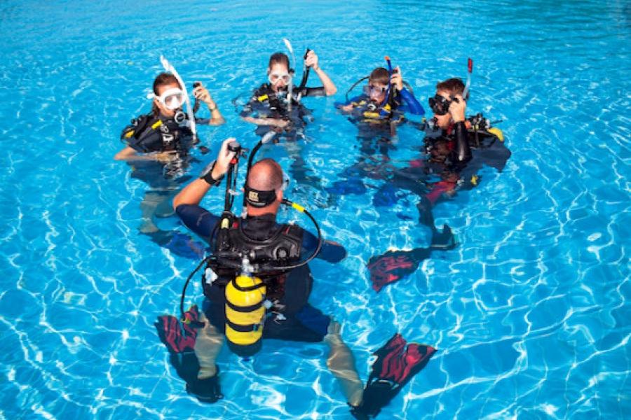 groupe de personnes faisant leur bapteme de plongée sous marine